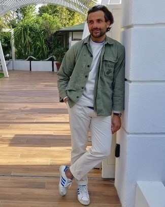Men's Outfits 2020: Wear a dark green shirt jacket with white chinos for a neat polished outfit. Feeling adventerous? Tone down this outfit by slipping into a pair of white and blue canvas low top sneakers.
