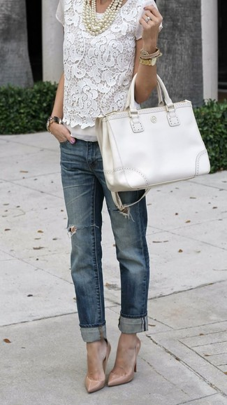 Effortlessly blurring the line between chic and casual, this combination of a white lace short sleeve blouse and navy ripped boyfriend jeans is likely to become one of your favorites. Choose a pair of cream leather pumps to va-va-voom your outfit.