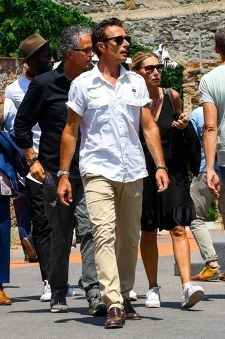 How to Wear Brown Leather Loafers For Men: Effortlessly blurring the line between cool and relaxed, this combination of a white short sleeve shirt and khaki chinos will likely become your favorite. Play up the dressiness of this ensemble a bit by slipping into brown leather loafers.