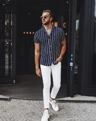 How to wear: navy and white vertical striped short sleeve shirt, white chinos, white leather low top sneakers, black sunglasses
