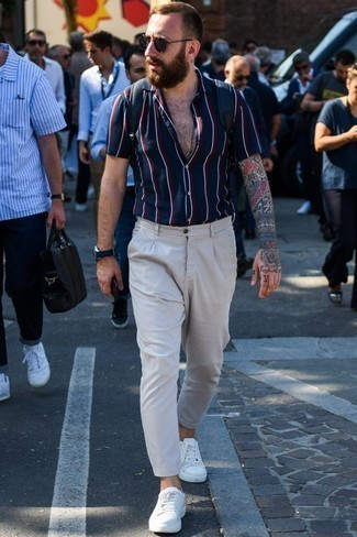 How to Wear Grey Chinos: If you enjoy a more relaxed approach to fashion, why not try teaming a navy vertical striped short sleeve shirt with grey chinos? A pair of white leather low top sneakers is a smart choice to finish this getup.