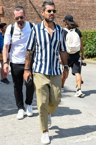 How to Wear a White and Navy Vertical Striped Short Sleeve Shirt For Men: Stand out among other gentlemen by wearing a white and navy vertical striped short sleeve shirt and khaki chinos. A nice pair of white canvas low top sneakers ties this ensemble together.