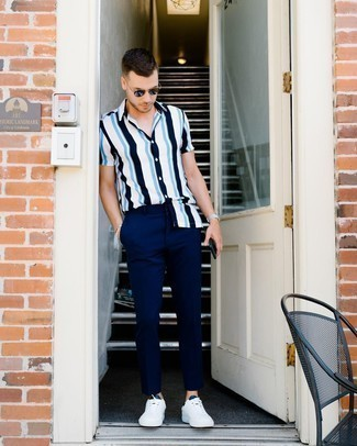 White and Navy Vertical Striped Short Sleeve Shirt Outfits For Men: This outfit with a white and navy vertical striped short sleeve shirt and navy chinos isn't super hard to score and leaves room to more experimentation. If you're wondering how to round off, a pair of white and navy leather low top sneakers is a tested option.