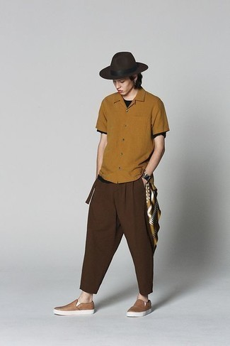 Black Crew-neck T-shirt Outfits For Men: This off-duty combo of a black crew-neck t-shirt and dark brown chinos is capable of taking on different forms depending on the way it's styled. When not sure as to the footwear, go with tan leather slip-on sneakers.
