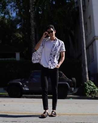 Black Leather Sandals Outfits For Men: This combo of a white and navy print short sleeve shirt and navy jeans is pulled together and yet it's comfortable enough and ready for anything. A pair of black leather sandals can effortlessly dial down an all-too-polished ensemble.