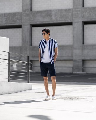 Navy Shorts Outfits For Men: A white and navy vertical striped short sleeve shirt and navy shorts are a great combination worth having in your daily collection. A pair of white canvas low top sneakers is very fitting here.