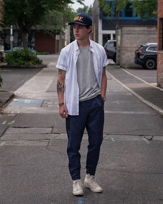 Beige Canvas High Top Sneakers Outfits For Men: We all seek practicality when it comes to styling, and this city casual combo of a white vertical striped short sleeve shirt and navy sweatpants is an amazing example of that. A cool pair of beige canvas high top sneakers pulls this look together.