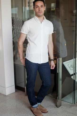 How to Wear a White Short Sleeve Shirt For Men: If you're on the hunt for a casual yet stylish outfit, consider wearing a white short sleeve shirt and navy jeans. Perk up your outfit with a pair of tan suede derby shoes.