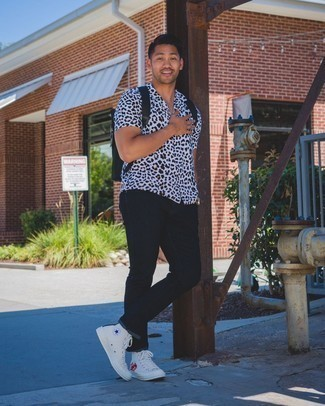 Black Canvas Backpack Outfits For Men: This off-duty pairing of a white leopard short sleeve shirt and a black canvas backpack is a life saver when you need to look good but have no extra time. Tone down the casualness of this look with a pair of white print canvas high top sneakers.