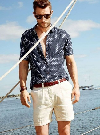 How to wear: navy and white polka dot short sleeve shirt, beige shorts, brown leather belt, dark brown sunglasses