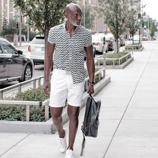 1200+ Outfits For Men After 50: This pairing of a white and black print short sleeve shirt and white shorts is hard proof that a pared down off-duty outfit can still be incredibly dapper. White canvas low top sneakers pull the look together. Like this style idea for a 50-something gentleman?
