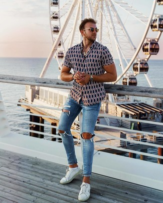 How to wear: navy print short sleeve shirt, blue ripped skinny jeans, white leather low top sneakers, brown sunglasses