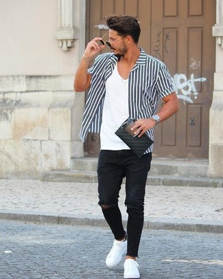 How to wear: black and white vertical striped short sleeve shirt, white v-neck t-shirt, black ripped skinny jeans, white leather low top sneakers