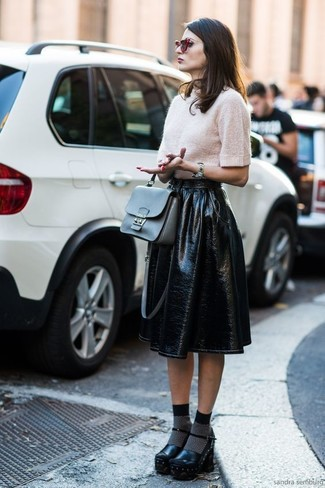 This pairing of a beige short sleeve sweater and a black leather full skirt is perfect for off-duty occasions. Elevate your getup with black chunky leather pumps. We're loving that this combination is great come cooler days.