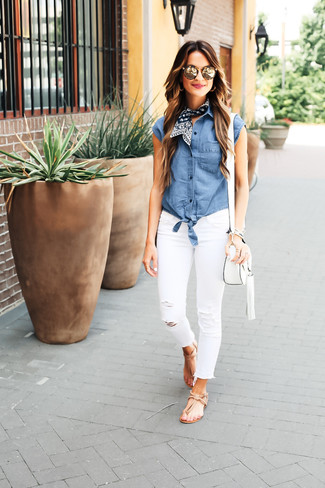 Effortlessly blurring the line between chic and casual, this combination of a blue chambray sleeveless button down shirt and white ripped slim jeans is likely to become one of your favorites. Want to go easy on the shoe front? Grab a pair of camel leather thong sandals for the day.