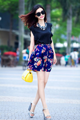 Opt for comfort in a black silk shell top and a blue floral pleated skirt. Lift up your look with silver embellished leather heeled sandals. As full-blown summer settled in, it's time for summery looks like this one.