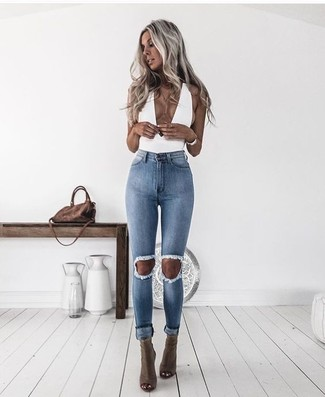 A white sleeveless top and light blue ripped skinny jeans are great essentials to incorporate into your current wardrobe. Olive boots are the right shoes here to get you noticed. This look is everything for those warm days of spring.