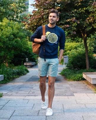 Cómo combinar: sudadera estampada azul marino, pantalones cortos estampados en verde menta, tenis de lona blancos, mochila en tabaco