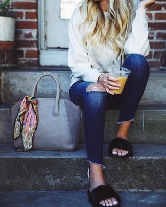 Cómo combinar: sudadera blanca, vaqueros pitillo desgastados azul marino, sandalias planas de pelo negras, bolsa tote de cuero gris