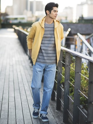 Cómo combinar: sudadera con capucha amarilla, camiseta con cuello circular de rayas horizontales gris, vaqueros celestes, tenis de lona azul marino