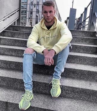 Cómo combinar: sudadera con capucha amarilla, camiseta con cuello circular negra, vaqueros pitillo desgastados celestes, deportivas en amarillo verdoso