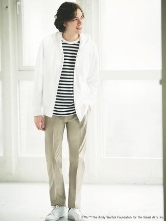 Cómo combinar: sudadera con capucha blanca, camiseta con cuello circular de rayas horizontales en blanco y negro, pantalón chino en beige, tenis de cuero blancos