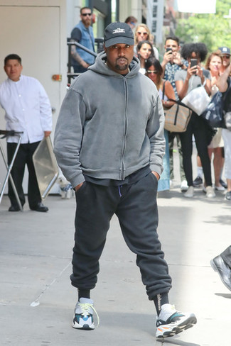 Cómo combinar: sudadera con capucha gris, camiseta con cuello circular negra, pantalón de chándal negro, deportivas en multicolor