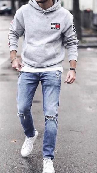 Cómo combinar: sudadera con capucha gris, camiseta con cuello circular blanca, vaqueros pitillo desgastados azules, tenis de lona blancos