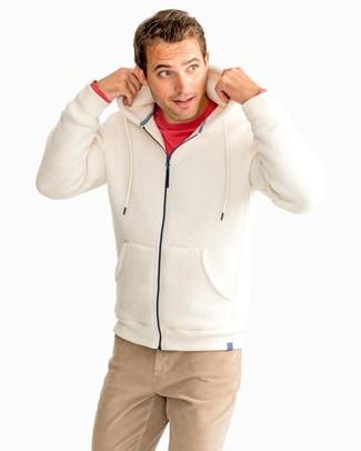 Cómo combinar: sudadera con capucha de forro polar en beige, camiseta de manga larga roja, pantalón chino marrón claro