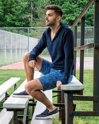 Cómo combinar: sudadera con capucha de punto azul marino, pantalones cortos estampados azules, zapatillas slip-on de lona azul marino
