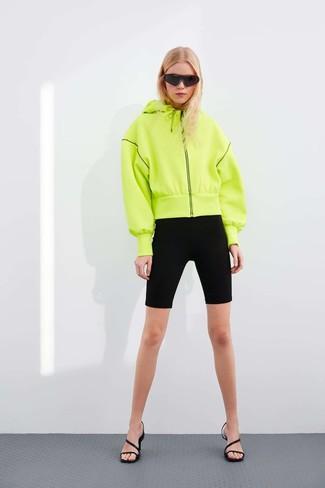 Cómo combinar: sudadera con capucha en amarillo verdoso, mallas ciclistas negras, sandalias de tacón de cuero negras, gafas de sol negras