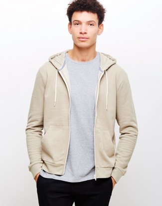 Cómo combinar: sudadera con capucha en beige, camiseta con cuello circular gris, pantalón chino negro