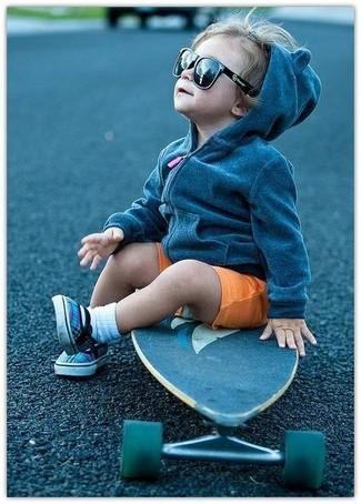 Cómo combinar: sudadera con capucha en gris oscuro, pantalones cortos naranjas, zapatillas azules, calcetines blancos