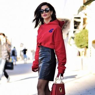 Cómo combinar: sudadera con capucha roja, minifalda de cuero negra, bolso de hombre de cuero rojo, gafas de sol negras