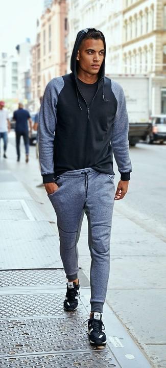 Cómo combinar: sudadera con capucha negra, camiseta con cuello circular negra, pantalón de chándal gris, deportivas negras