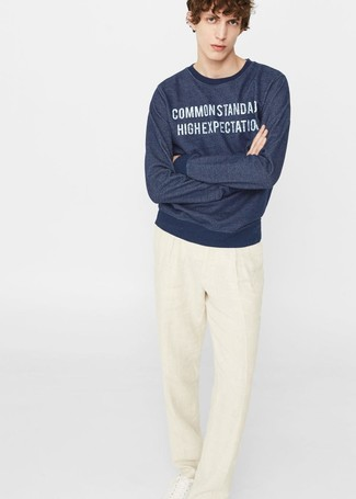 Cómo combinar: sudadera estampada azul marino, pantalón de vestir de lino en beige, tenis de cuero blancos