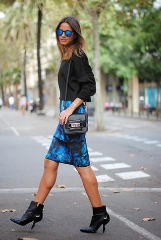 Cómo combinar: sudadera negra, falda lápiz estampada azul, botines de cuero negros, bolso bandolera de cuero negro