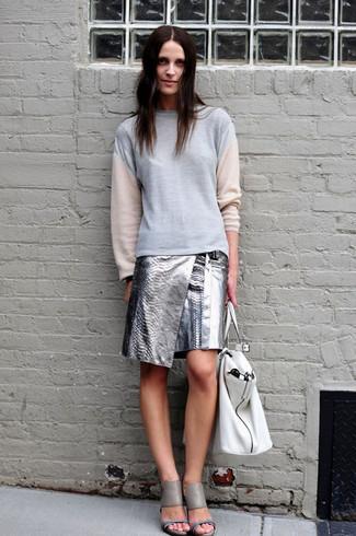 Cómo combinar: sudadera gris, minifalda de cuero plateada, sandalias de tacón de cuero grises, bolsa tote de cuero blanca