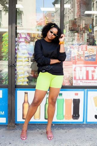 Cómo combinar: sudadera negra, mallas ciclistas en amarillo verdoso, chinelas de cuero rosa, riñonera de nylon negra
