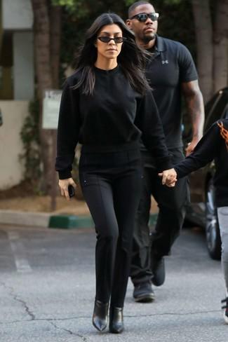 Cómo combinar: sudadera negra, pantalones pitillo negros, botines de cuero negros, gafas de sol negras
