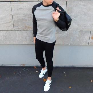 Cómo combinar: sudadera gris, pantalón de chándal negro, tenis de cuero en blanco y negro, bolsa de viaje de cuero negra