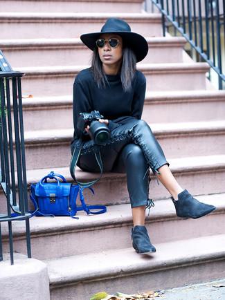 Cómo combinar: sudadera negra, pantalones pitillo de cuero negros, botines chelsea de ante negros, bolso bandolera de cuero azul