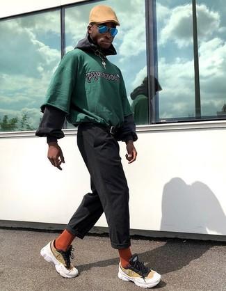 Cómo combinar: sudadera estampada verde, sudadera con capucha negra, pantalón chino negro, deportivas amarillas