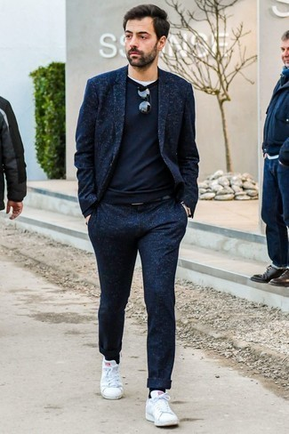 How to Wear a Black Leather Belt For Men: For on-trend menswear style without the need to sacrifice on functionality, we love this combination of a navy wool suit and a black leather belt. Let your outfit coordination sensibilities truly shine by rounding off this look with a pair of white leather low top sneakers.