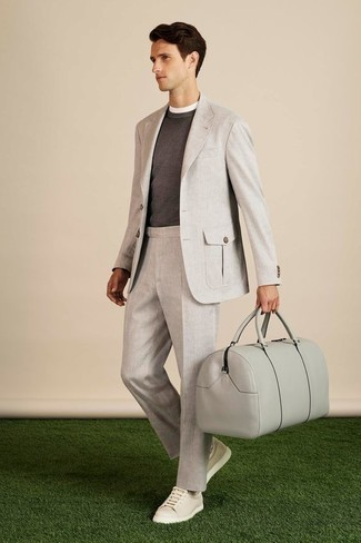 How to Wear a Grey Suit: You'll be amazed at how easy it is to get dressed this way. Just a grey suit and a charcoal crew-neck sweater. Complete your getup with a pair of beige leather low top sneakers to avoid looking too polished.