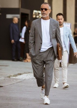How to Wear a Brown Leather Zip Pouch For Men: If you feel more confident in comfortable clothes, you'll love this stylish combination of a grey suit and a brown leather zip pouch. Finishing with white athletic shoes is a fail-safe way to bring a more laid-back spin to this look.