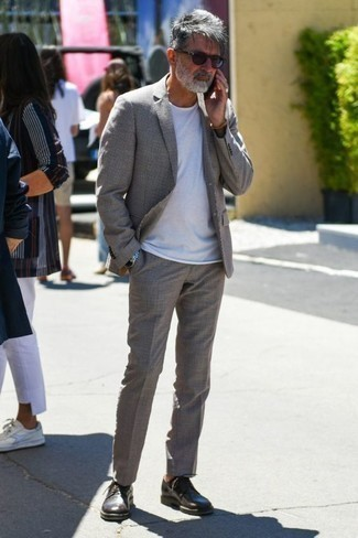 Men's Looks & Outfits: What To Wear In 2020: Try teaming a grey suit with a white crew-neck t-shirt to achieve an interesting and well-executed outfit. Change up your ensemble by wearing a pair of dark brown leather derby shoes.