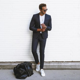 How to wear: black vertical striped suit, white crew-neck t-shirt, white leather low top sneakers, black leather holdall