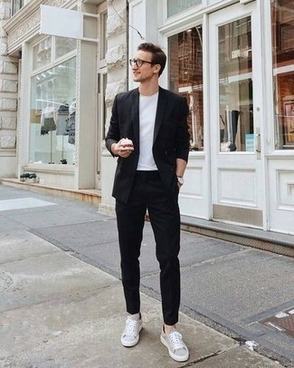 How to Wear a Black Suit: This combination of a black suit and a white crew-neck t-shirt spells manly sophistication and class. Make your ensemble more functional by rounding off with grey canvas low top sneakers.