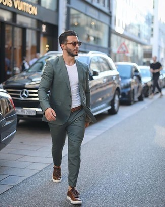 Brown Woven Leather Belt Outfits For Men: A dark green suit looks so casual and cool when paired with a brown woven leather belt. Let your outfit coordination skills truly shine by finishing off this getup with a pair of brown leather low top sneakers.